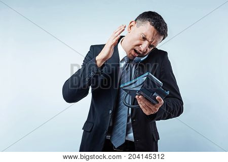 Are you kidding. Nervous man of business gesturing and getting angry during a business telephone conversation over the light background.