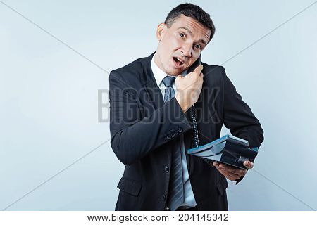 What did you say. Waist up shot of a confused male worker in a black suit holding an office telephone and listening to somebody during a phone conversation with his face grimacing into the camera.