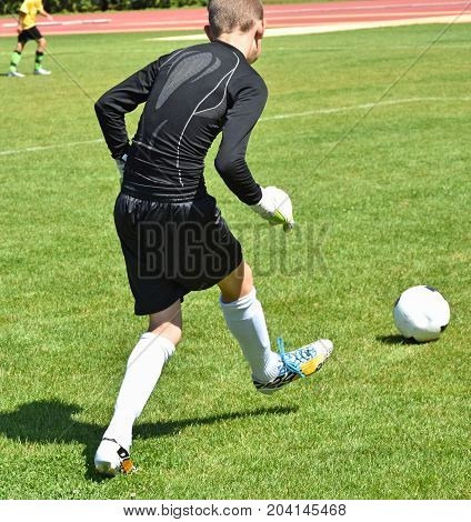 Young goalkeeper kicks the ball off on the field
