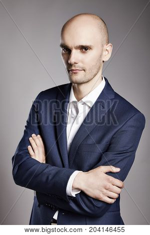 Portrait of young bald businessman looking at camera.