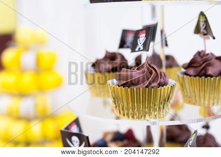Close-up of cupcakes on stand in yellow and black colors pirate theme for kids birthday party
