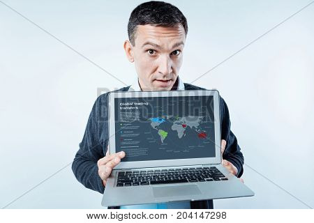 Did you know. Inquisitive businessman looking into the camera with his eyed wide opened while showing a laptop with a global trading transfers map on the screen.