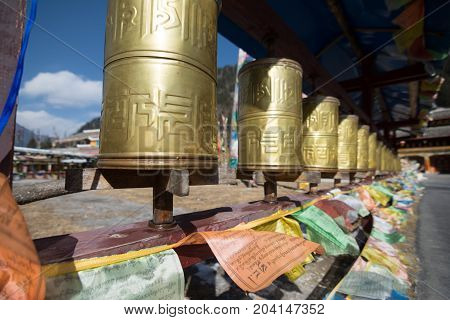 Buddhist prayer wheels in a Tibetan monastery. Prayer wheels with a written mantra.