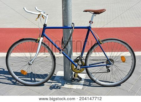 Bicycle chained to a metal pole in the city