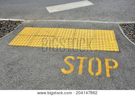 Stop sign on the asphalt at the road crossing