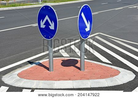 Arrow road signs at the road crossing in the city