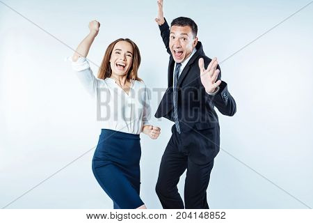 Hurray. Extremely emotional entrepreneurs getting excited and jumping high while celebrating their successful project over the light background.