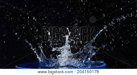 Blue water drops falling down. Black background
