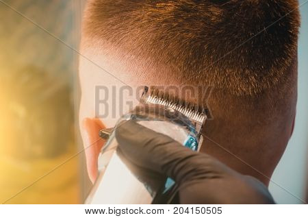 Close up shot of man getting trendy haircut at barber shop. Male hairstylist serving client making haircut using machine and comb.