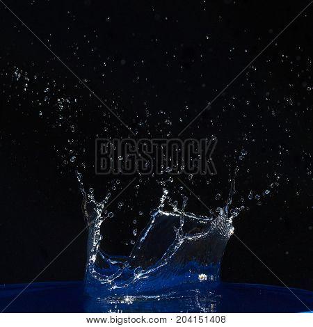 Splash of water crown on blue surface. Black background