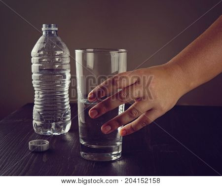 A woman's hand takes a glass of water a glass with clean fresh water and a plastic bottle on the table