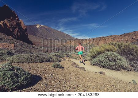 Young woman trail running in mountains on sunny summer day. Female runner jogging and working out in nature cross country running on rocky trail footpath on Tenerife Canary Islands