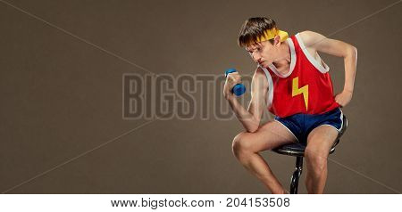 A thin funny guy in sports clothes in the pose of the Greek thinker.