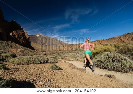 Trail running woman in mountains on sunny summer day. Beauty female runner jogging and exercising outdoors in nature trail running training on rocky trail footpath on Tenerife Canary Islands