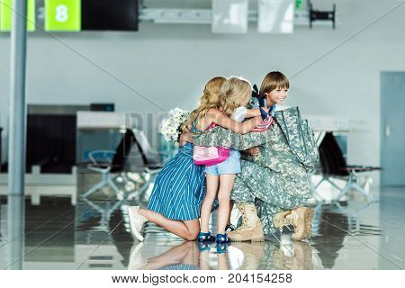 Family Hugging Father At Airport