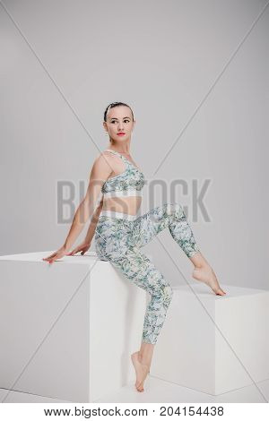 nice girl in grey sport suit posing in studio, trendy woman sitting in studio and looking to the side