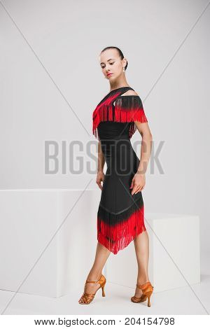 pretty woman in red and black dress in studio, young girl posing while standing in a white studio