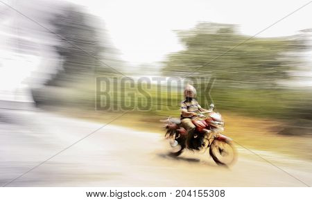 Fast motorbike drive driver sitting on motorbike blurred photo to show motion