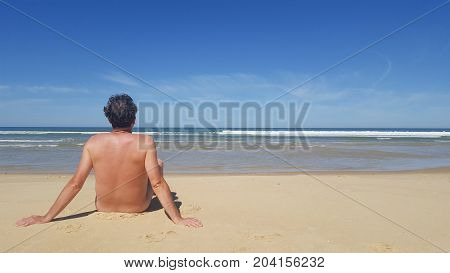 Colour Portrait Photo Of A Naked Man Sitting Alone On The Beach