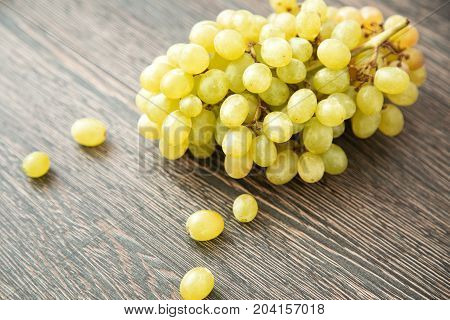 Brunch of green frapes, fruits of autumn on wood background