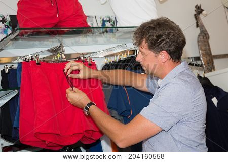 Man Chooses A Shirt In The Store Center