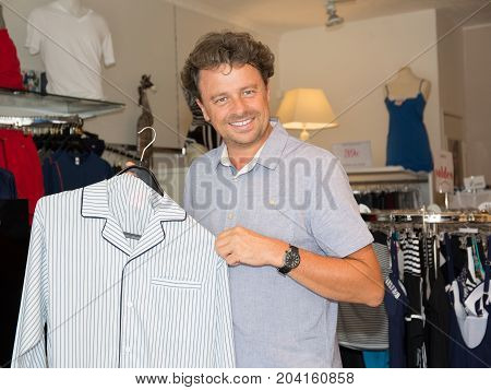 Man In Shirt Choosing Jacket In Mall Or Clothing Store