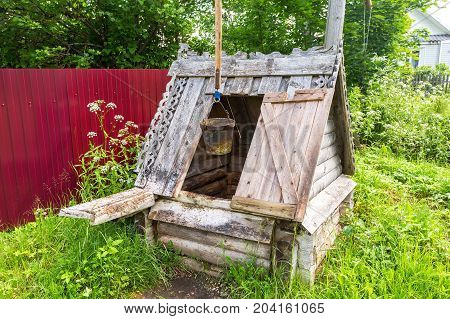 Old village wooden water well at the countryside in summer day