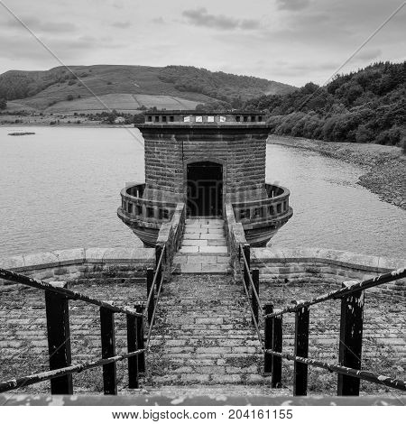 Water Tower Ladybower Reservoir Derbyshire. Steps leading down to water tower. Square crop image in black and white.
