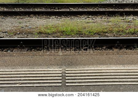railway station train track close up with blind people marking