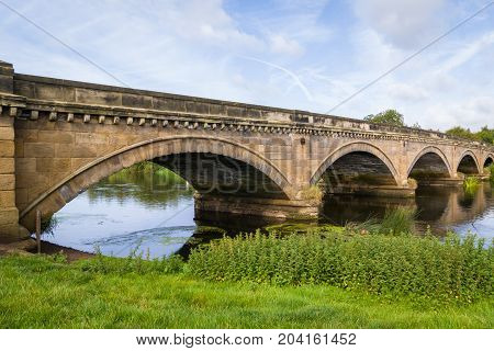 Stone Bridge over The River Trent between Repton and Willington Derbyshire. Showing the river, cloudy sunny blue sky, green folage foreground, reflection of bridge in water.
