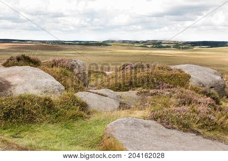 View from Stanage Edge Derbyshire. Looking from the rocks in the foreground on to the moorland and then on to the cloudy sky.