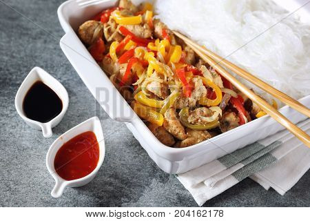 Asian food: fried chicken with tricolor bell peppers and rice vermicelli in ceramic crockery soy sauce piquant red sauce and chopsticks on dark background