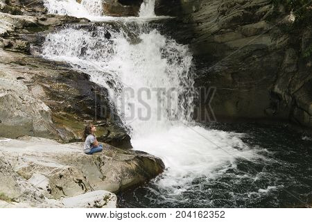 Girl Sitting On A Rock Next To The Waterfall.