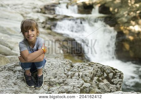 Girl sitting on a rock next to the Waterfall of the bucket in the Selva de Irati in Navarra Spain.