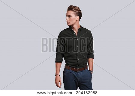 Confidence and charisma. Good looking young man keeping hand in pocket and looking away while standing against grey background