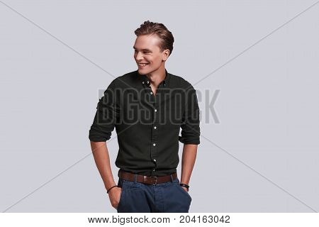 Irresistible man. Good looking young man keeping hands in pockets and smiling while standing against grey background