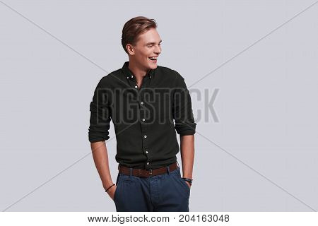Used to look perfect. Good looking young man keeping hands in pockets and laughing while standing against grey background