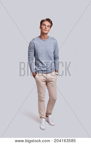 Good look! Full length of handsome young man looking at camera and keeping hands in pockets while standing against grey background