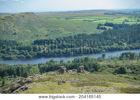 Family picnicking on Dartmoor National Park. Taken from Leather Tor looking towards Burrator reservoir.