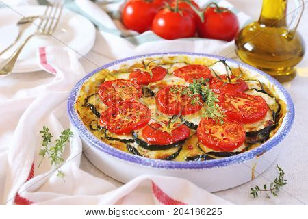 Zucchini and tomatoes gratin with bechamel sauce and cheese thyme garnish
