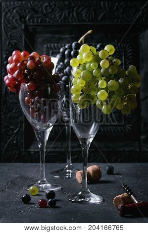 Variety of three type fresh ripe grapes dark blue, red and green in different standing wine glasses with old corkscrew over black texture background.