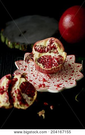 Useful antioxidant pomegranate, lies with the dark countertops. One in broken with juicy flesh. Framed by green leaves. Healthy eating during the vitamin deficiency