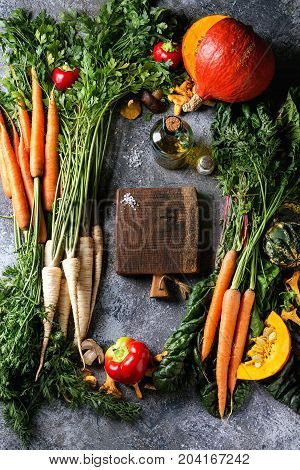 Variety of autumn harvest vegetables carrot, parsnip, chard, paprika, hokkaido pumpkin, mushrooms. Empty wooden chopping board, olive oil, salt over gray texture background. Cooking concept. Top view