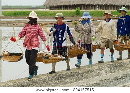 HUAHIN, THAILAND - MAY 13, 2008: Unidentified people work at the salt farm in Huahin, Thailand. Salt production is one of the main industries in Huahin area it brings modest income to many local families.