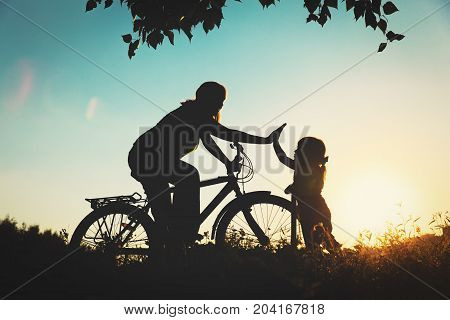 mother and little daughter riding bike and scooter at sunset, active family