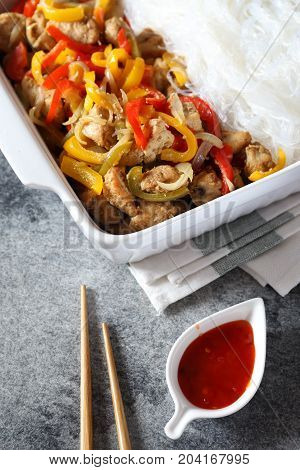 Asian food: fried chicken with tricolor bell peppers and rice vermicelli in ceramic crockery piquant red sauce and chopsticks. Top view on dark background