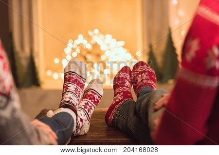 Couple In Knitted Socks Near Fireplace