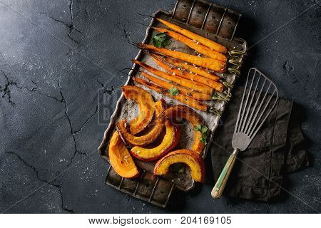 Roasted young whole carrot and sliced pumpkin with greens and sea salt. Served on vintage metal tray over black texture background. Top view with space