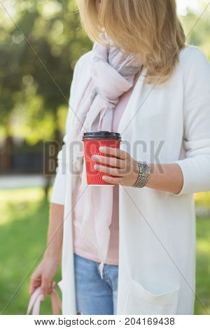One young woman with red cup of coffee to go in morning.