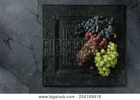 Variety of three type fresh ripe grapes dark blue, red and green on black metal ornate tray over dark texture background. Top view with space